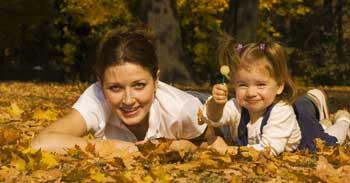 Picture a mother and her daughter outside, playing in the leaves and having fun!