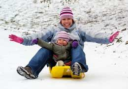 Mom sledding safely with child - Outdoor Winter Safety Tips